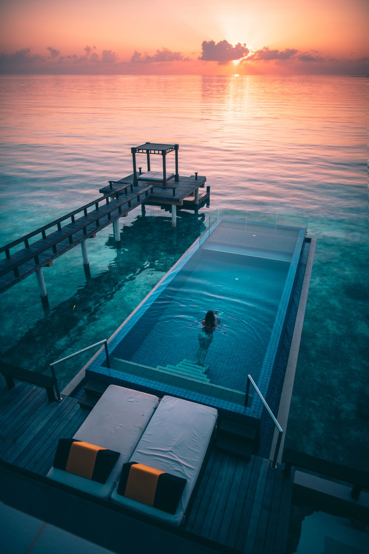 woman swimming in infinity pool at sunrise