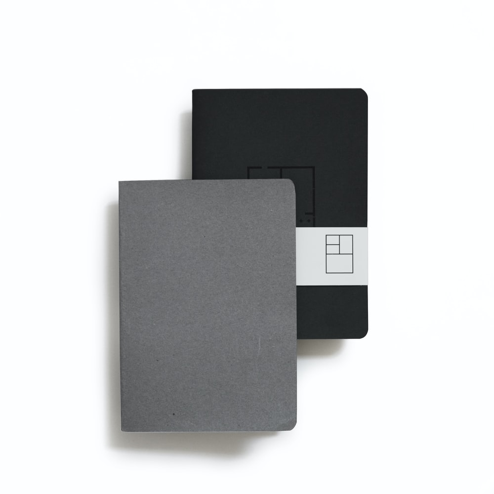 two black and gray book planners on white background