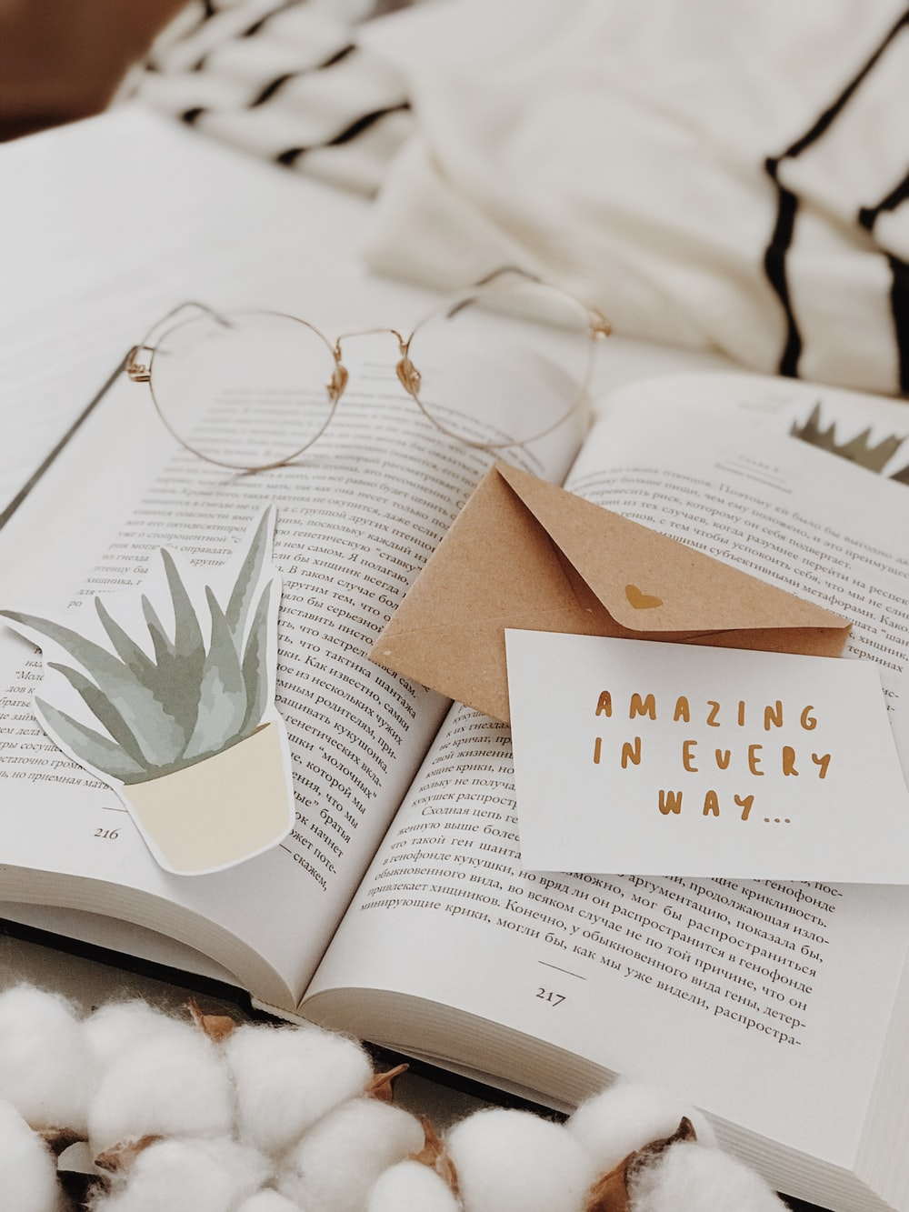 eyeglasses on book near envelope
