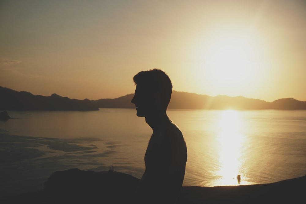 silhouette of man beside body of water during golden hour