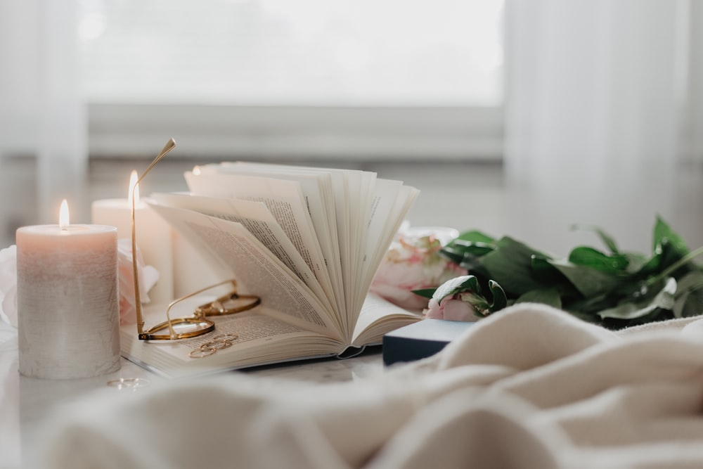white book on table with burning candle