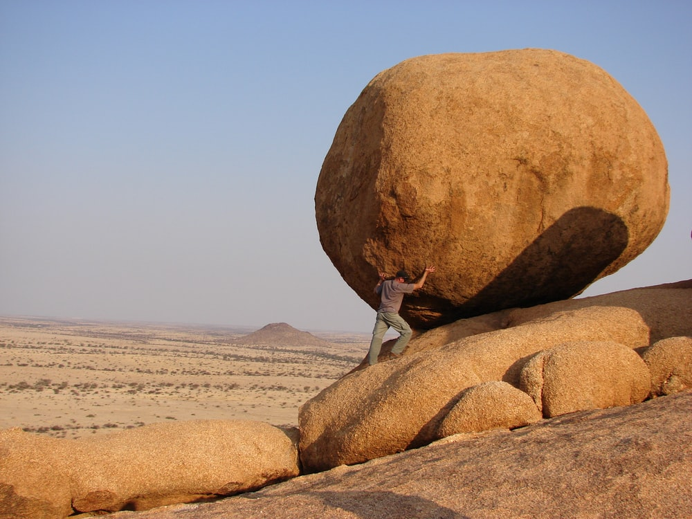 man standing beside rock formation