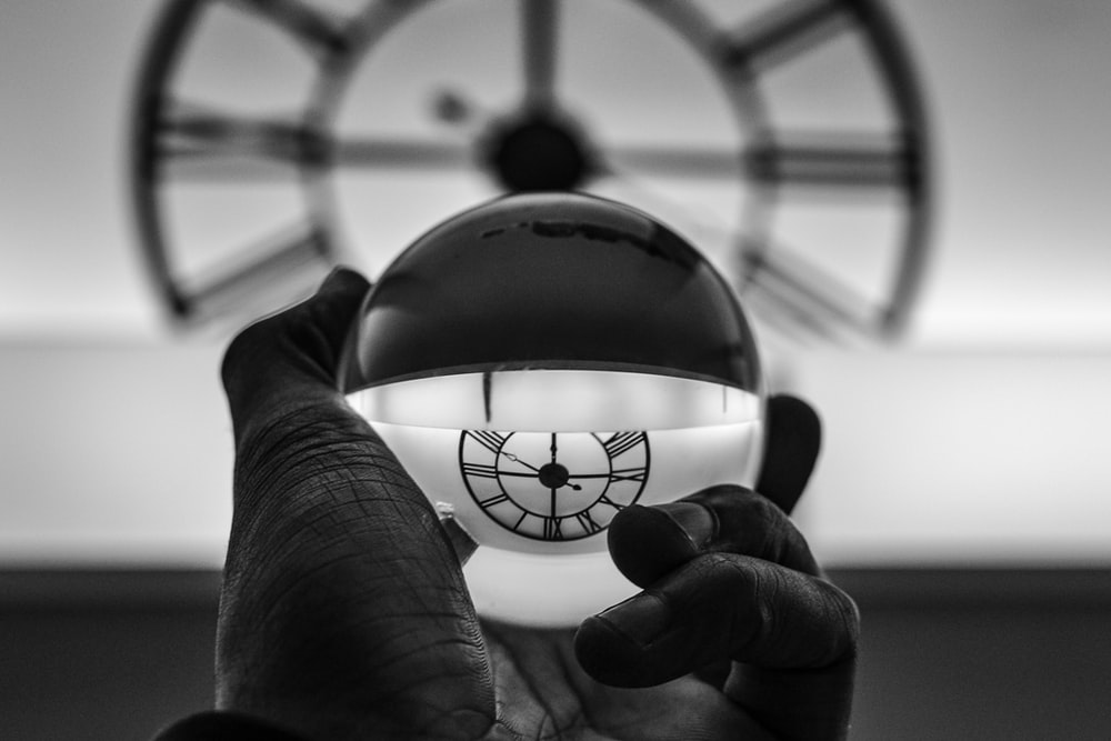 grayscale photography of person holding glass ball