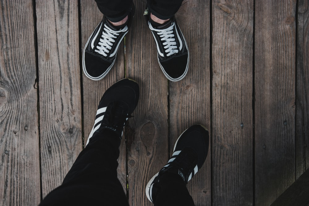 person wearing black-and-white Vans Old Skool shoes