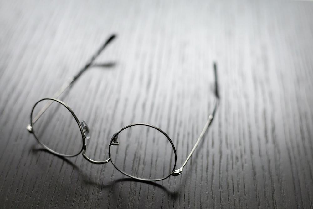 grey framed eyeglasses on wooden surface