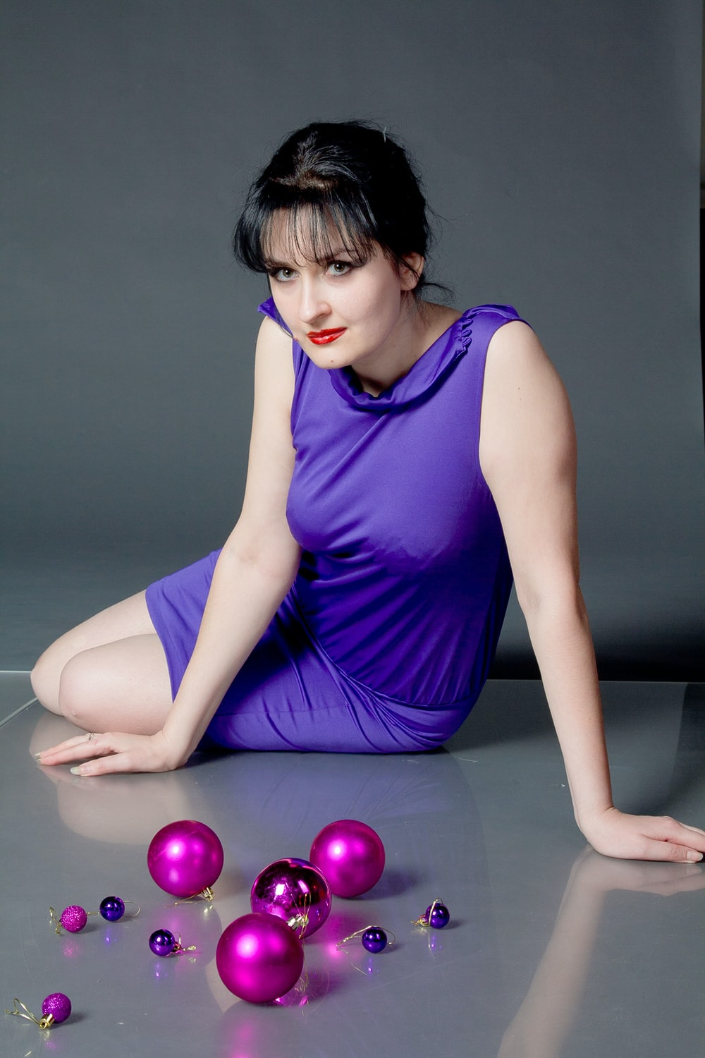 woman sitting on floor in front of baubles
