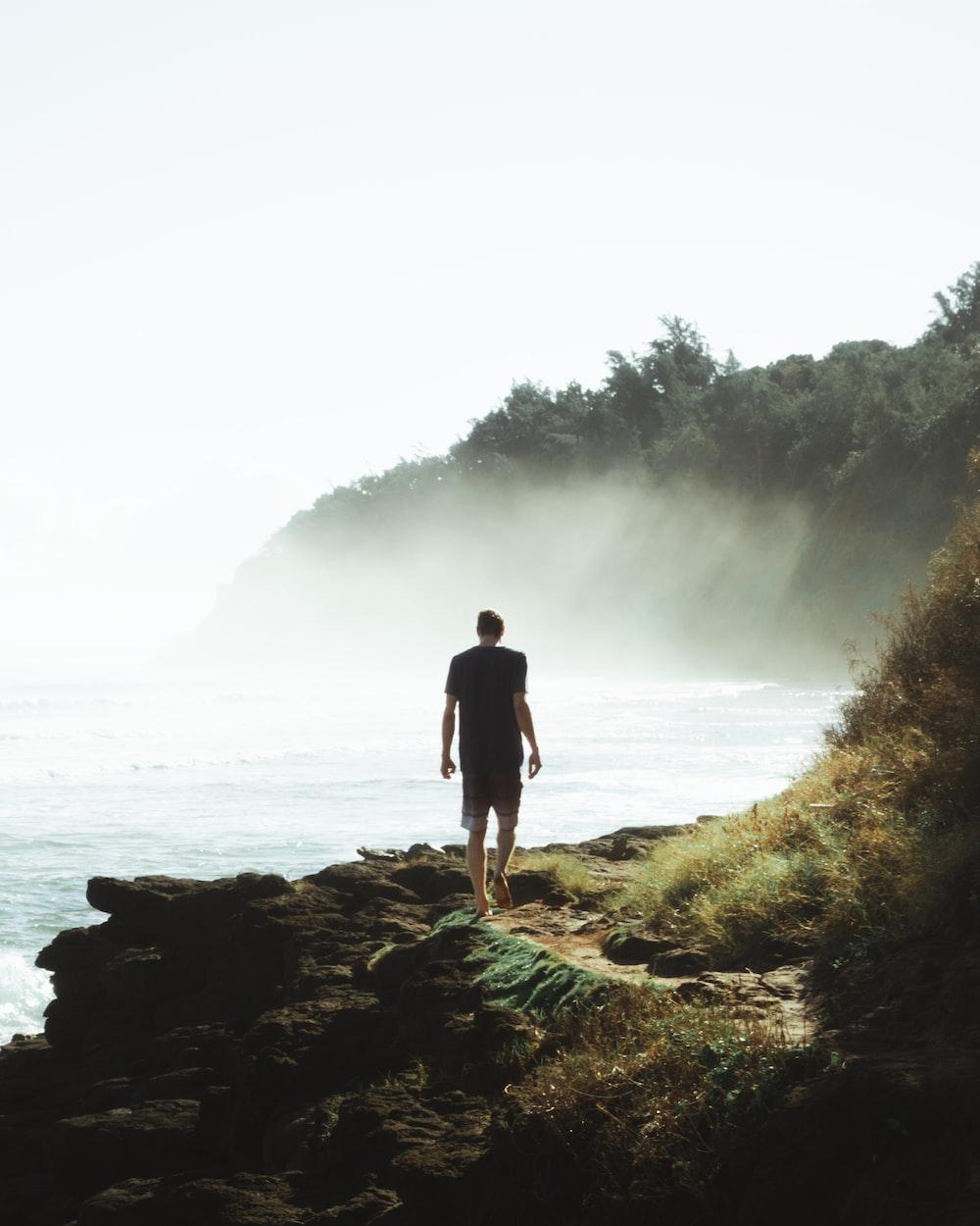 man in black walking on a seaside cliff