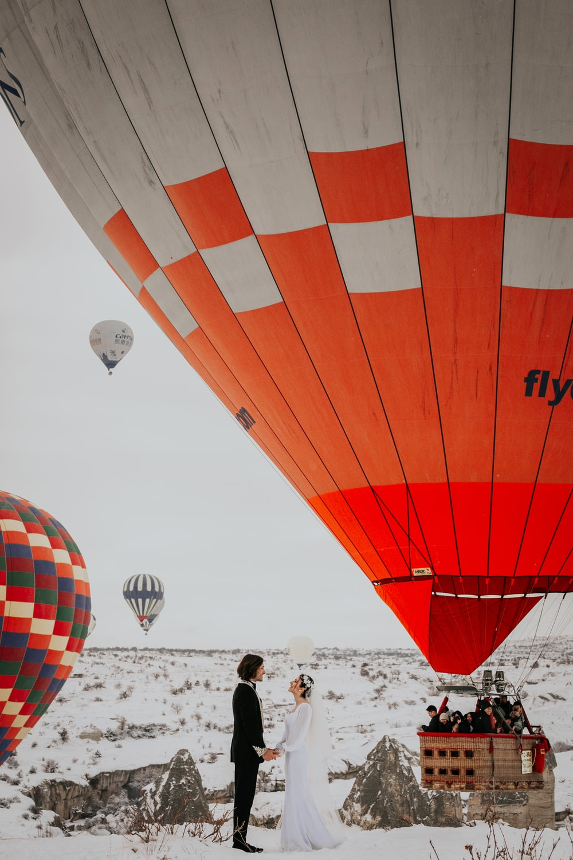 groom and bride near hot air balloons
