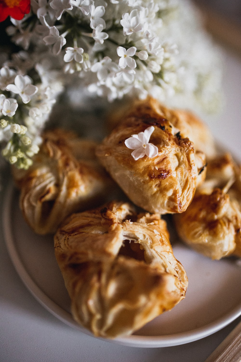 brown pastries on plated beside white flowers