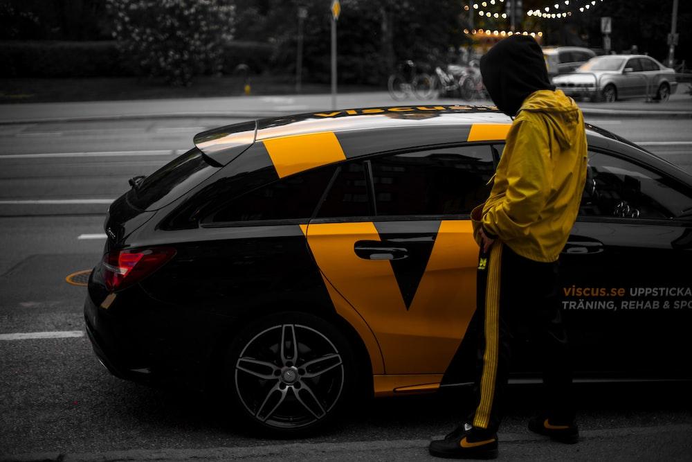 person near black and orange hatchback