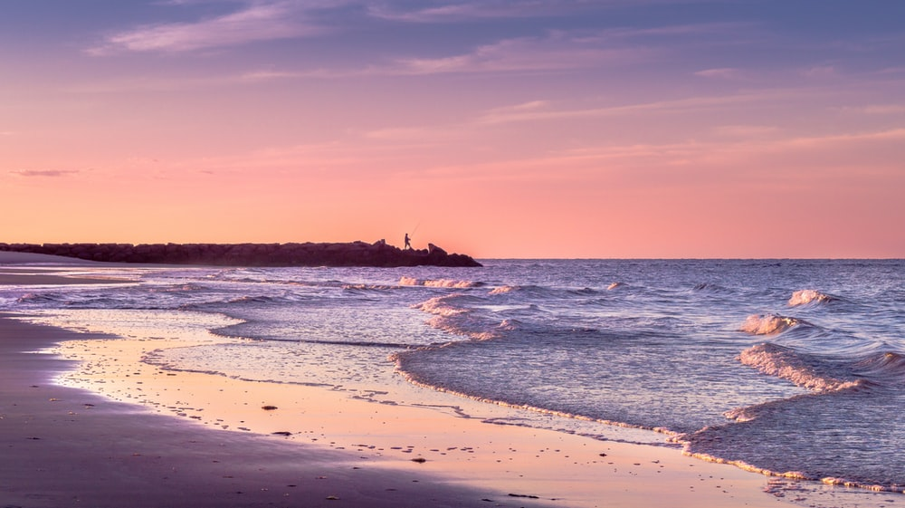 seashore viewing calm sea under orange skies