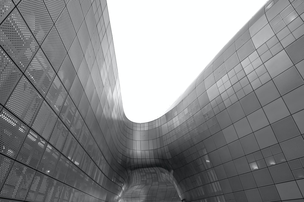 grayscale photo of glass walled building