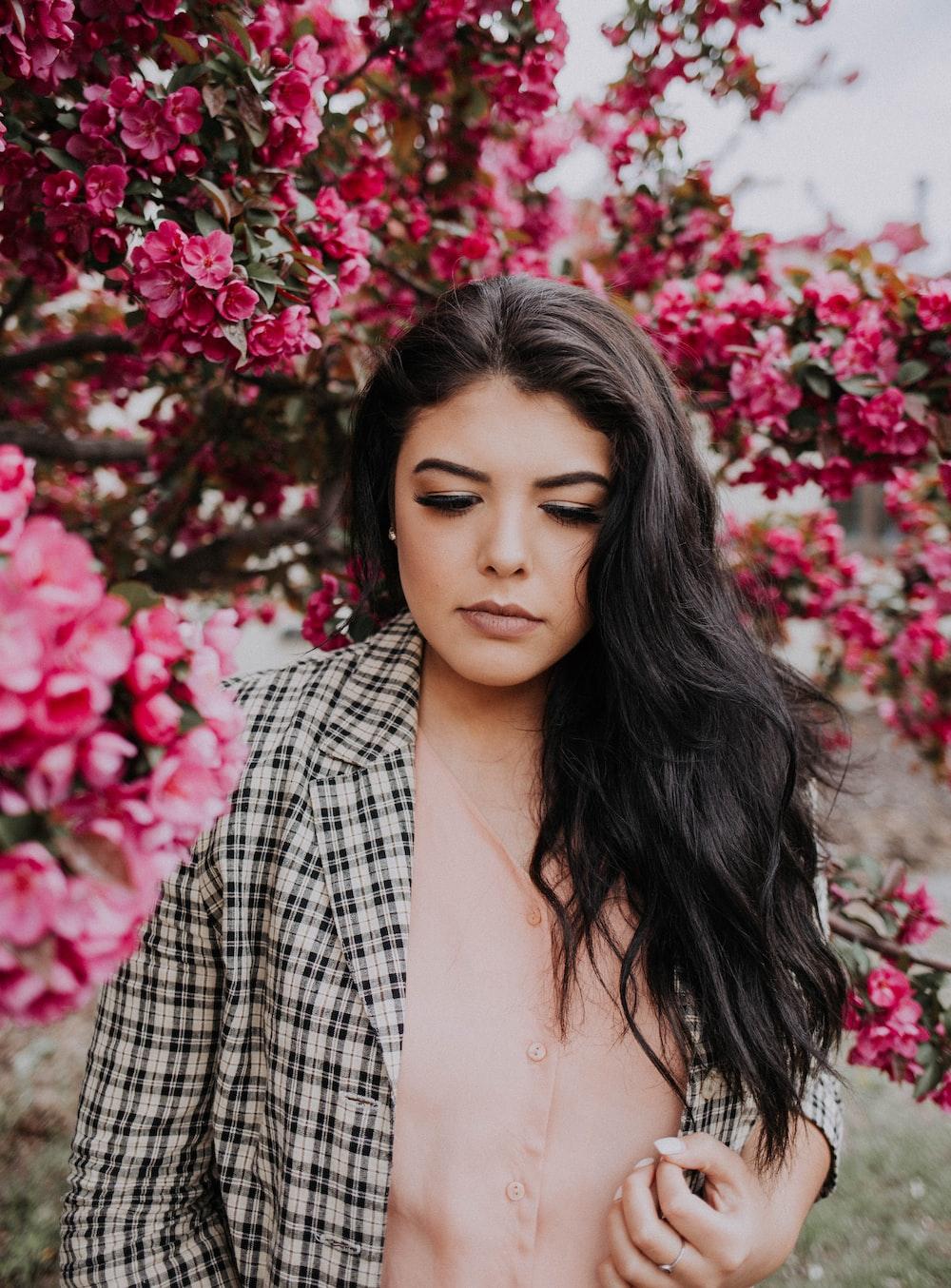 woman standing near pink flowers