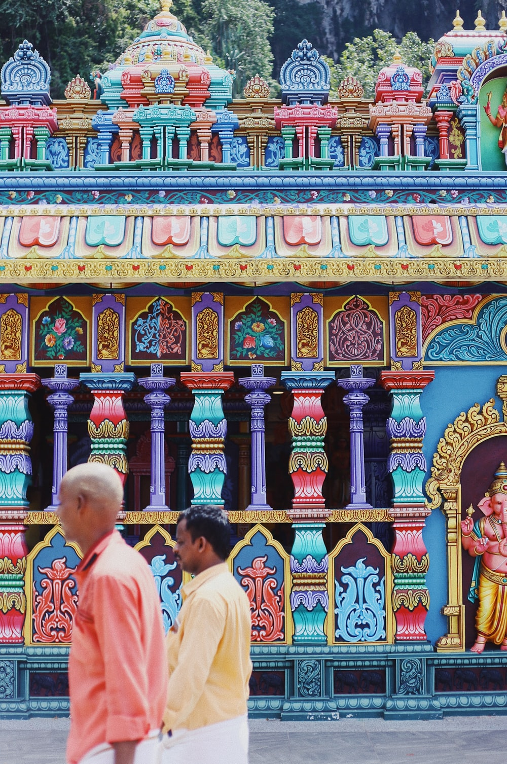 two men walking in front of multicolored building with Ganesha statue