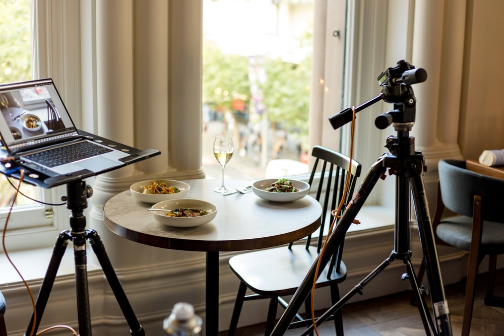 laptop computer near camera and table with food
