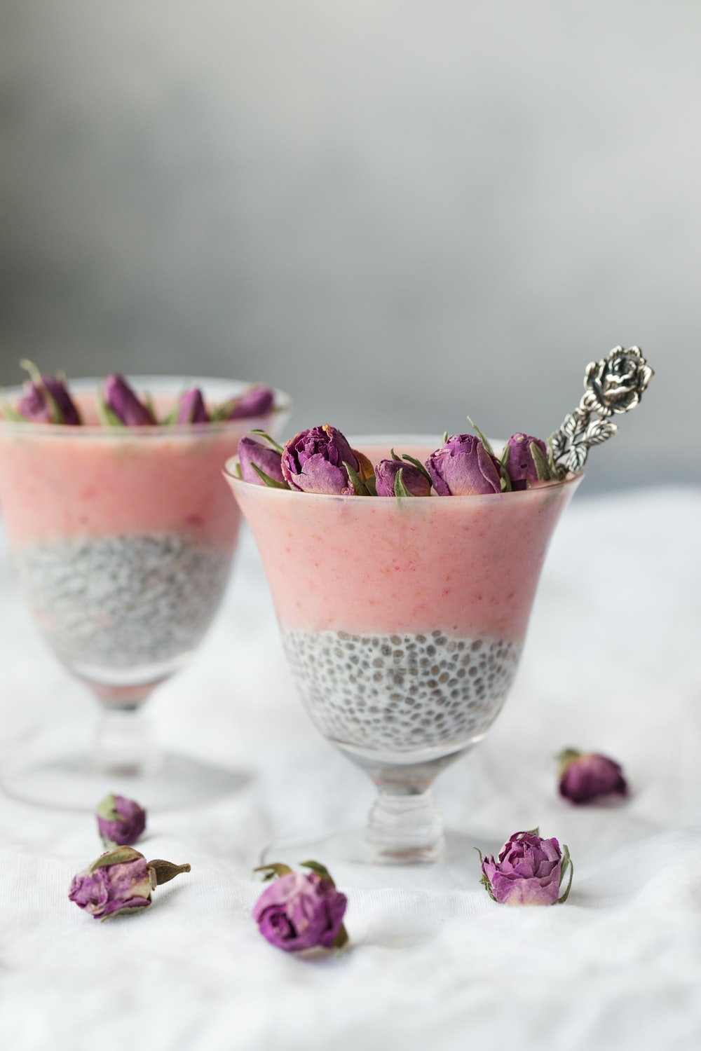 two pink tapioca dessert topped with pink rose buds