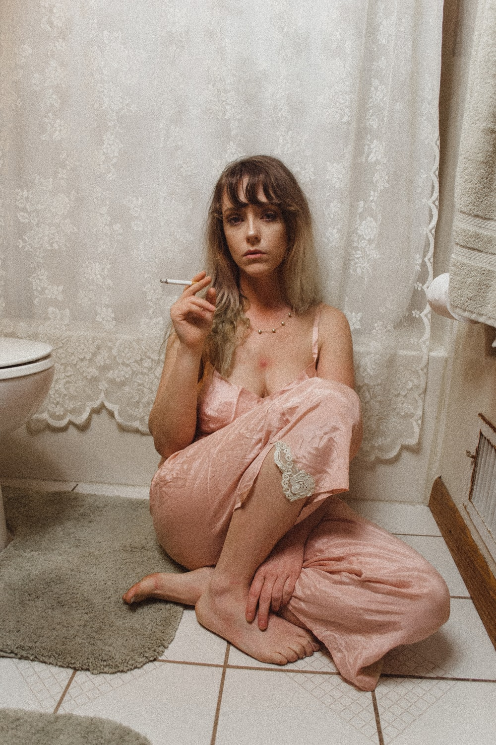 sitting woman wearing pajama pants smoking inside bathroom