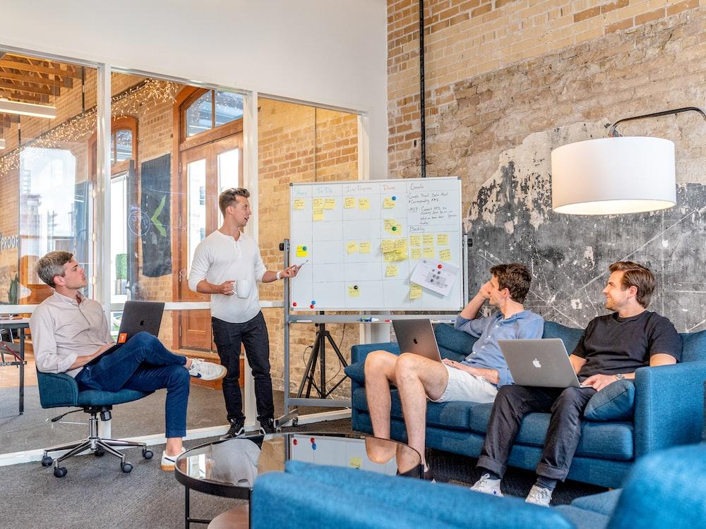 three men sitting while using laptops and watching man beside whiteboard