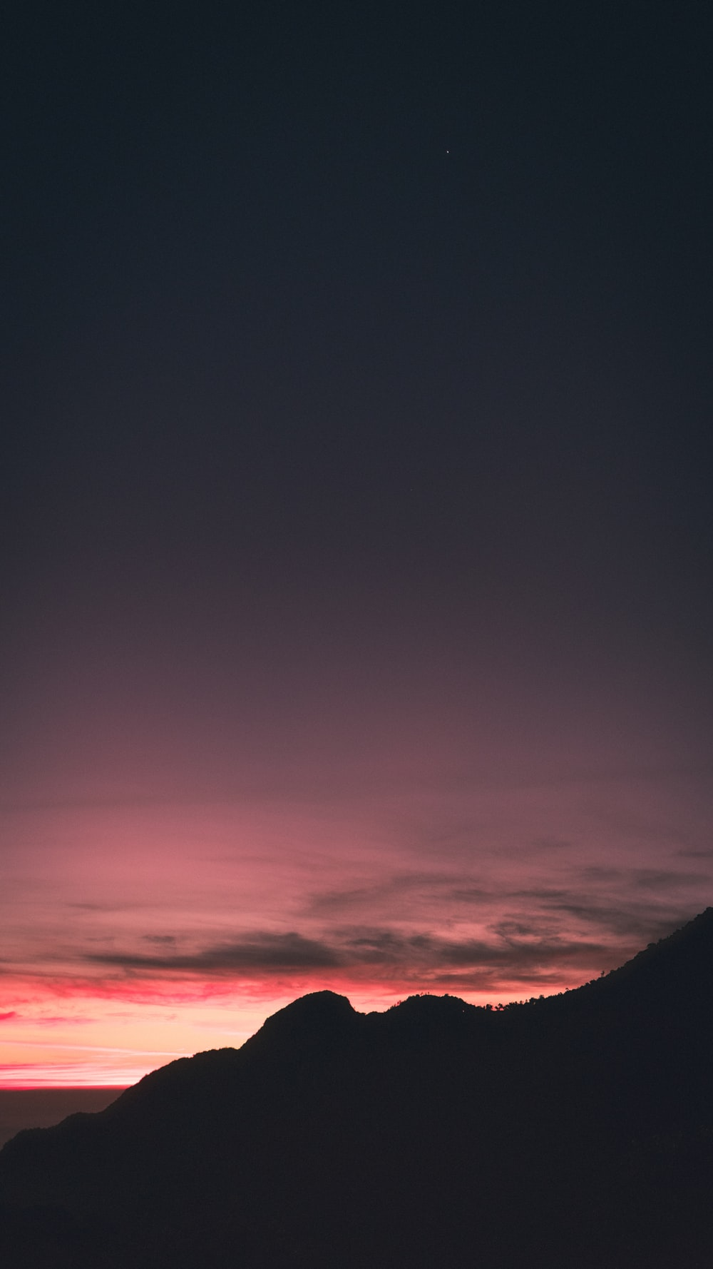 pink and grey sky over mountain during sunset