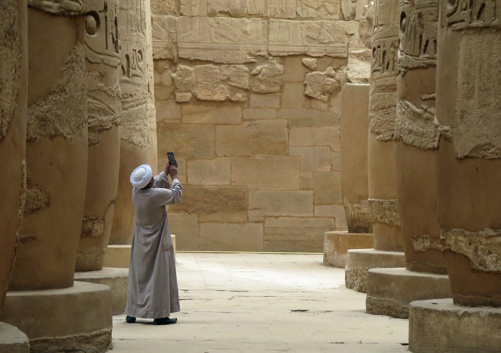 man wearing thobe taking photo\