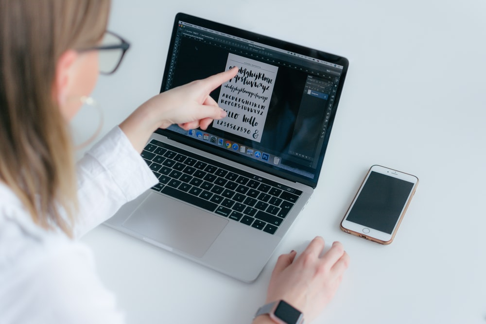 woman pointing MacBook Pro while using Magic Mouse