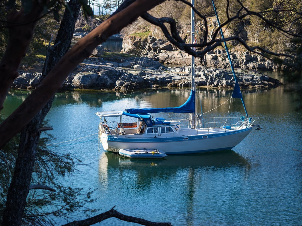 white sailing boat on body of water