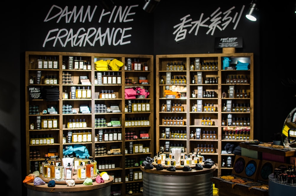 fragrance bottles and boxes on wooden rack and tables