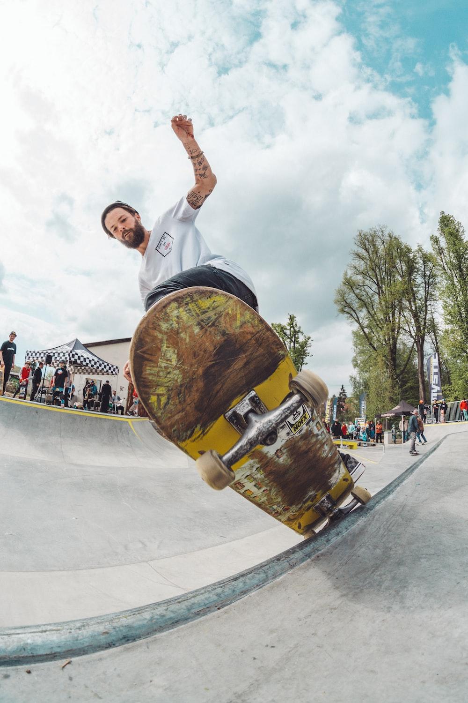 man wearing white shirt doing skateboard trick
