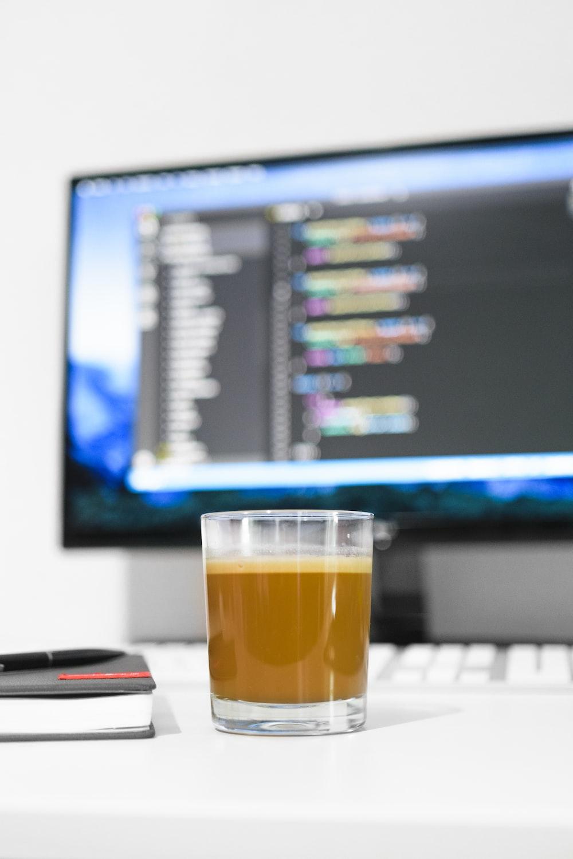 filled glass near monitor