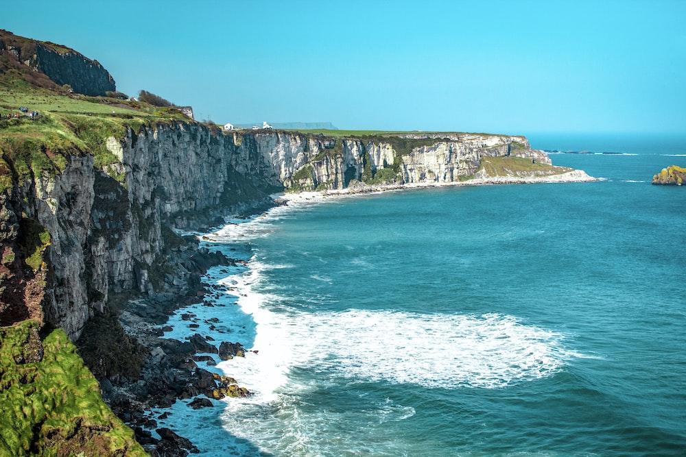 white rock cliff beside body of water'