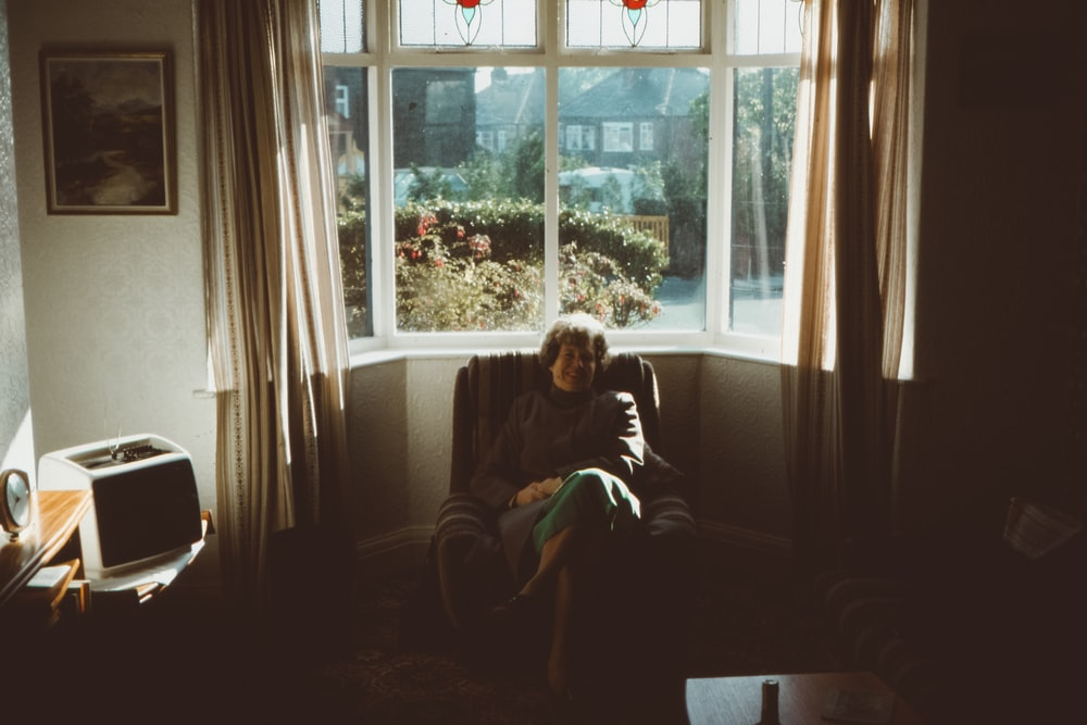 woman sitting on front of window