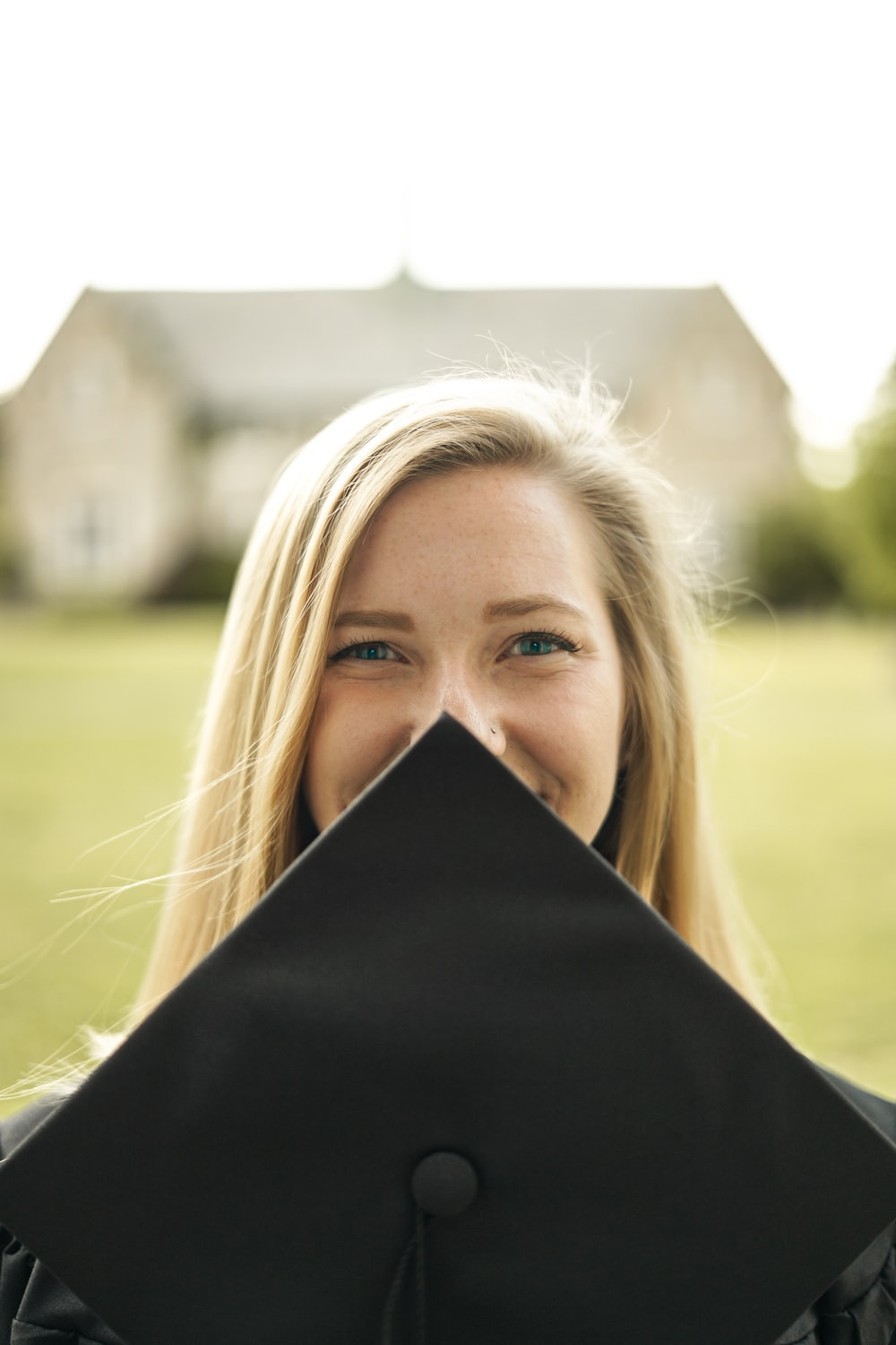 woman covering her face with black mortar board