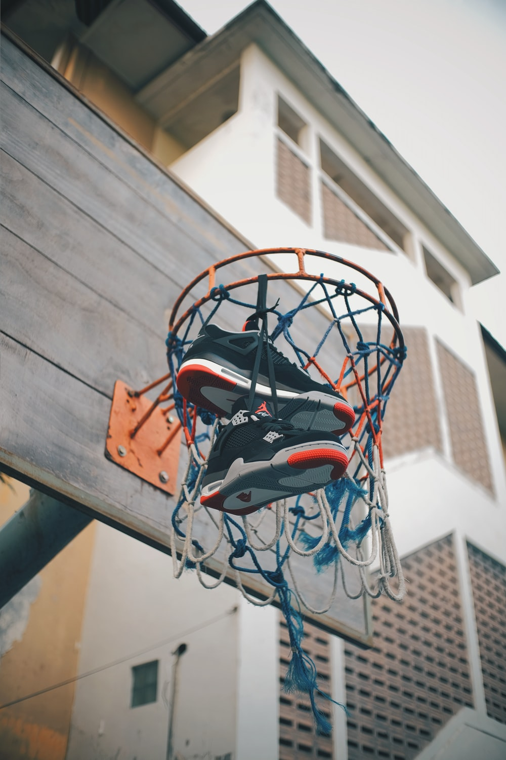 Air Jordan shoes in basketball hoop hanging on net during daytime