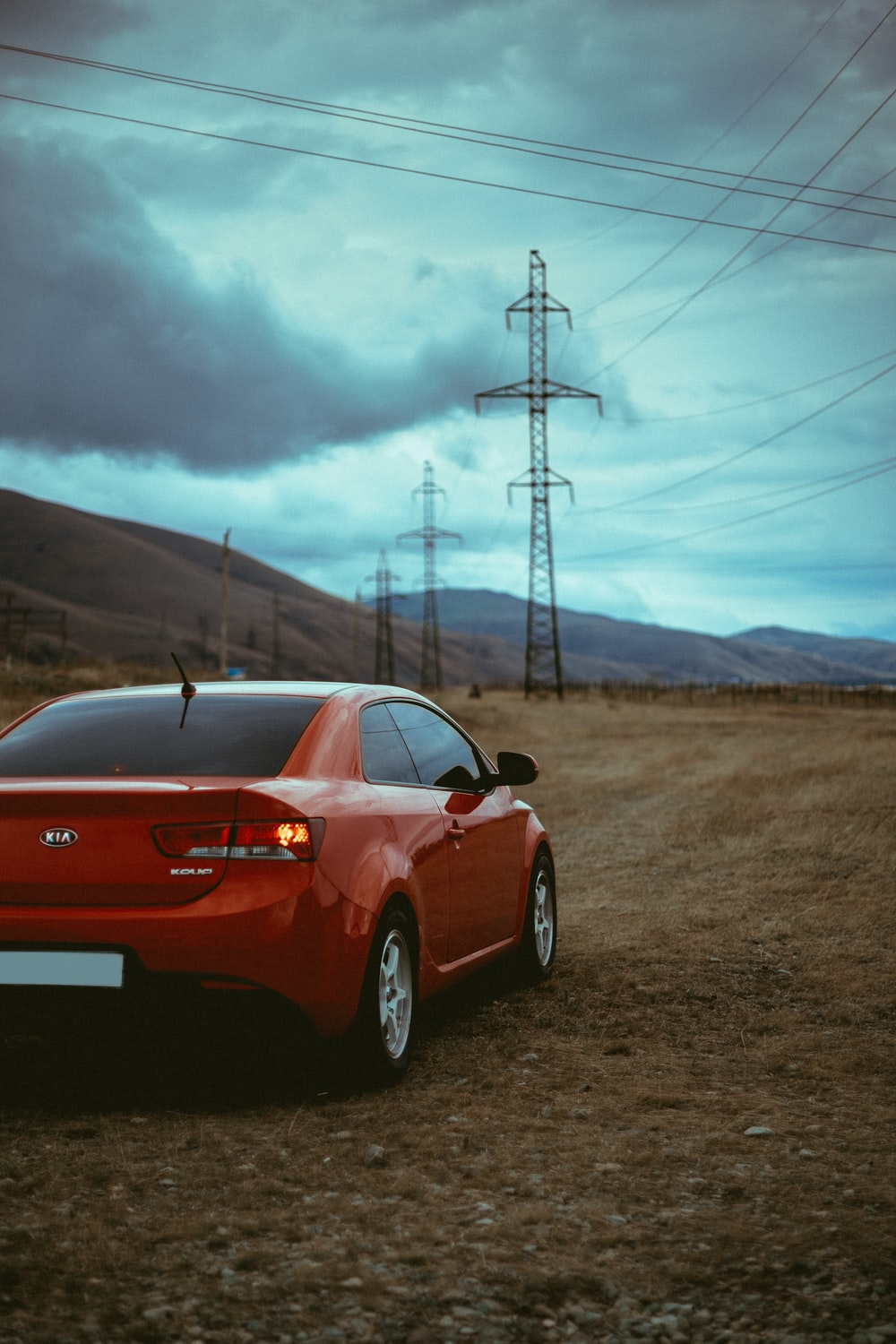 red Hyundai coupe near transmission tower