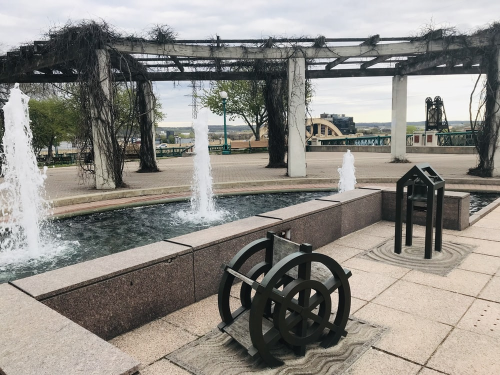 water fountain under gray clouds at daytime