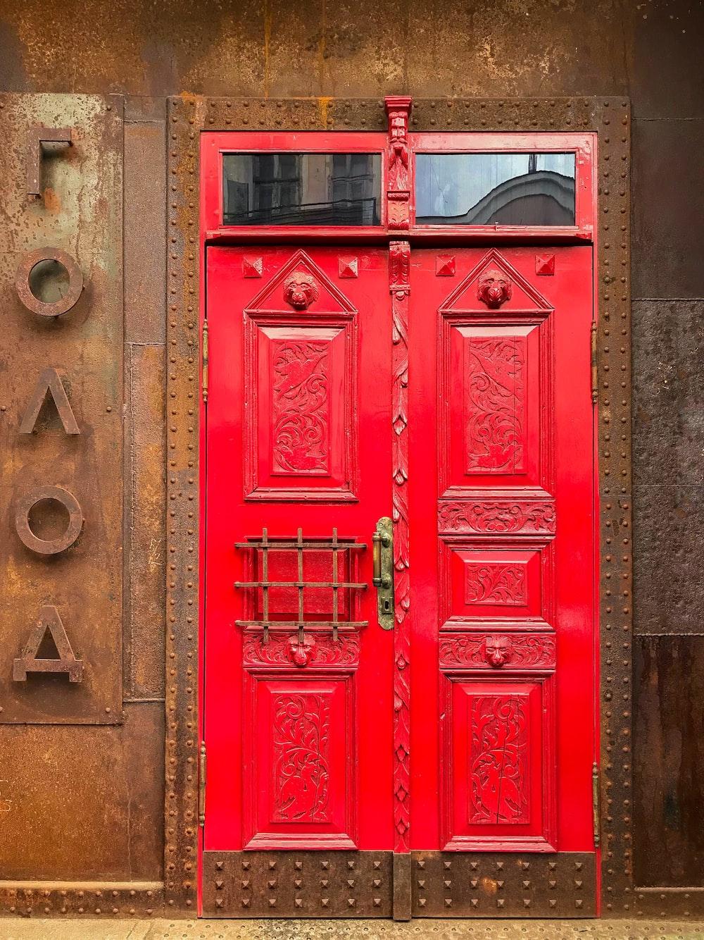 red painted door on brown rustic metal wall