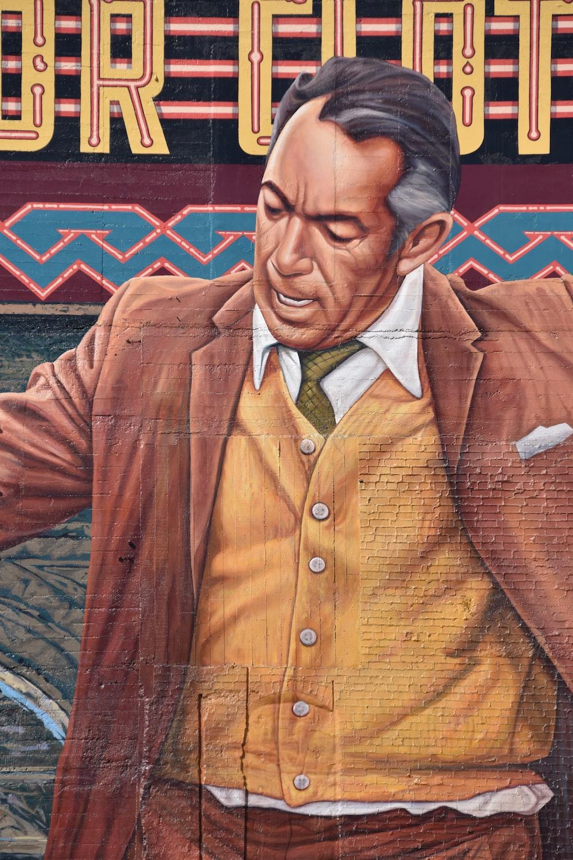 man wearing brown jacket painting