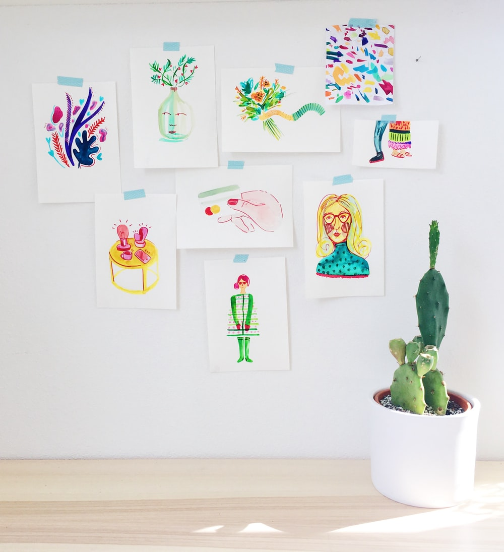 assorted-color abstract paintings on wall near green cactus plant in white pot