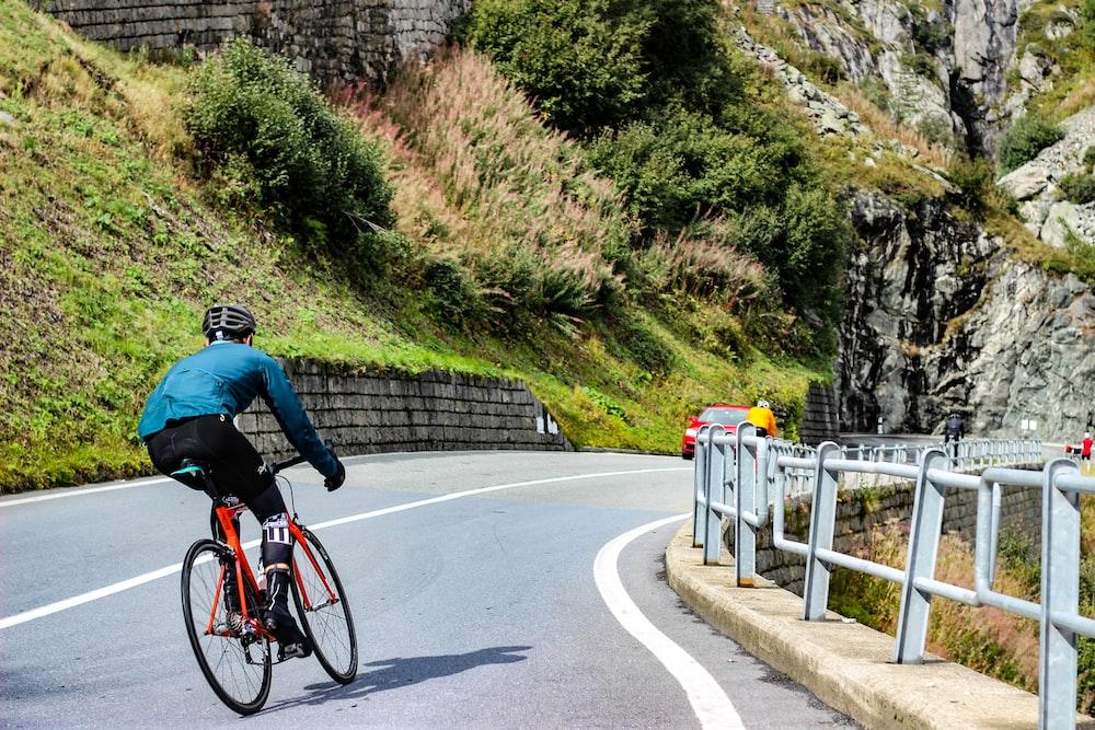 man riding mountain bike in road during daytime