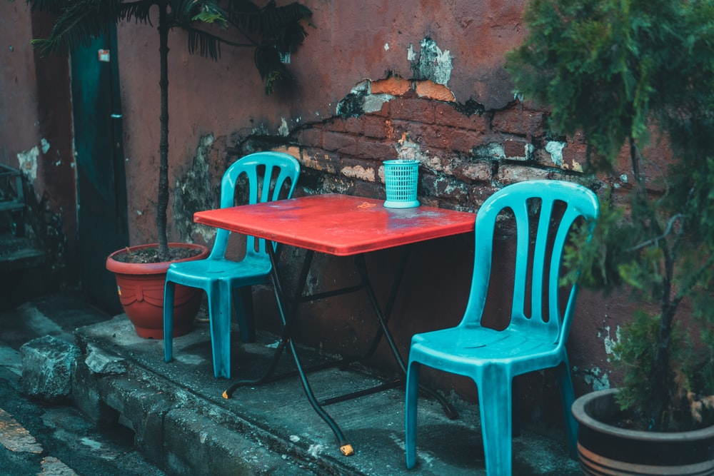 red and black folding table with between two blue plastic chairs