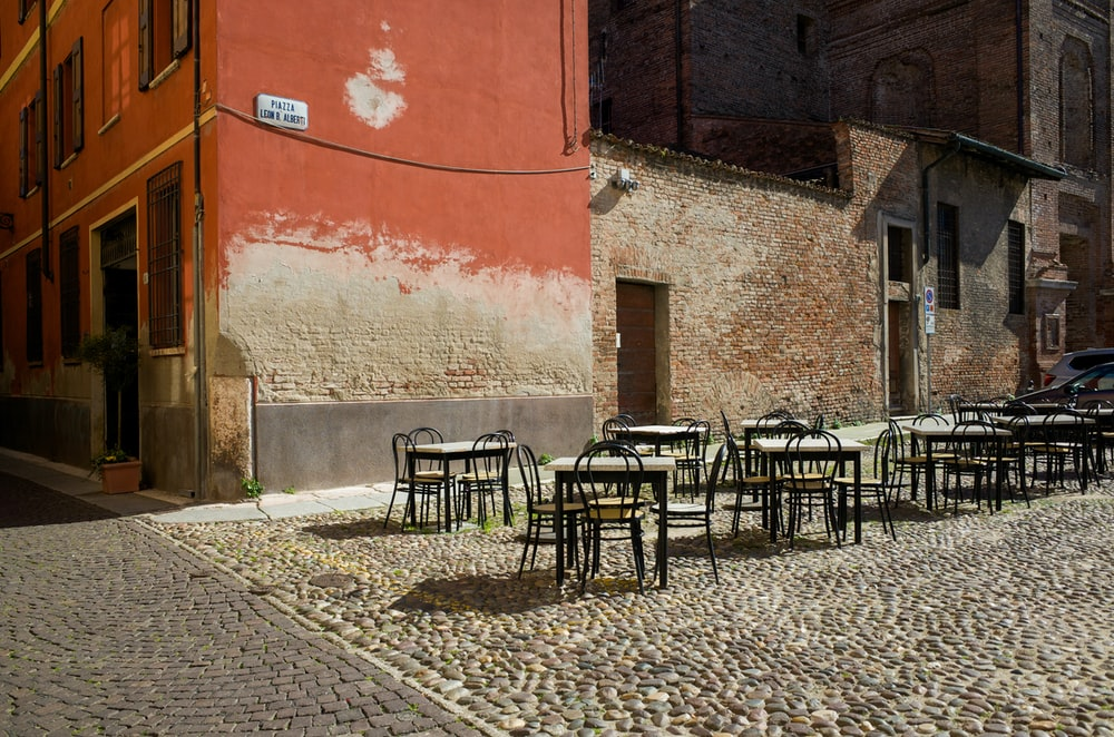 black steel chairs and tables outside building during daytime