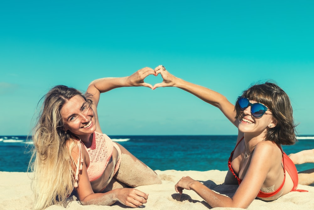 two women lying on seashore joining hands forming heart