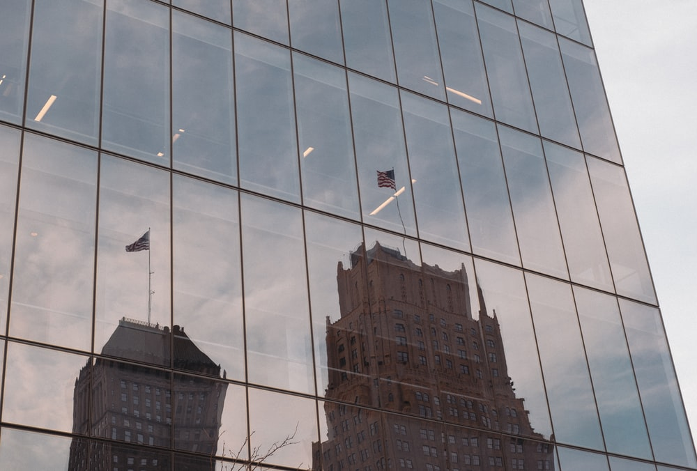 building with US flag reflected on glass building