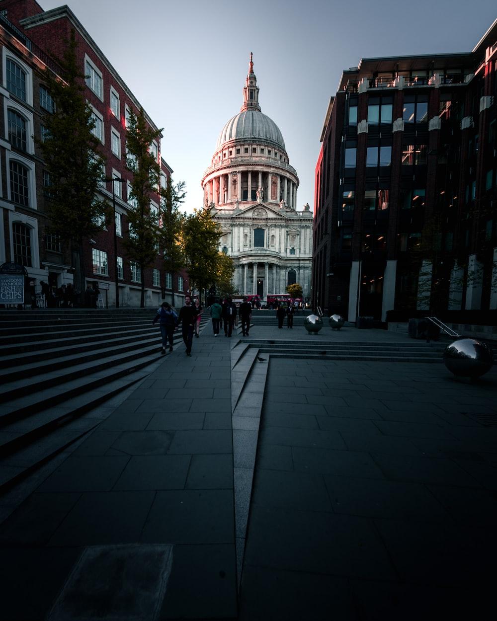 people walking towards white building during daytime