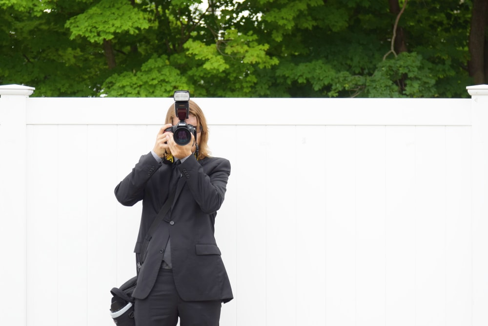person in black suit jacket using DSLR camera