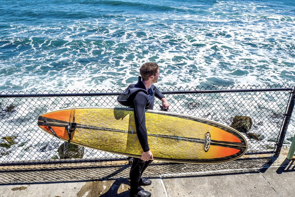 man holding yellow and black surfboard near sea during daytime