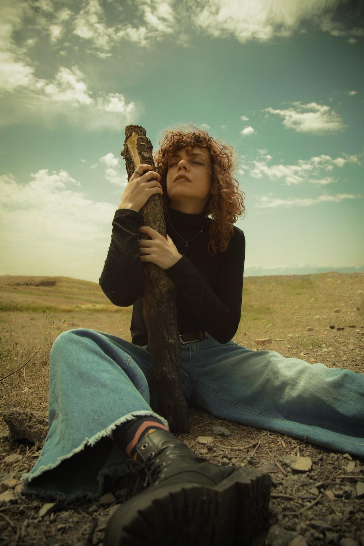 woman holding tree log sitting on ground