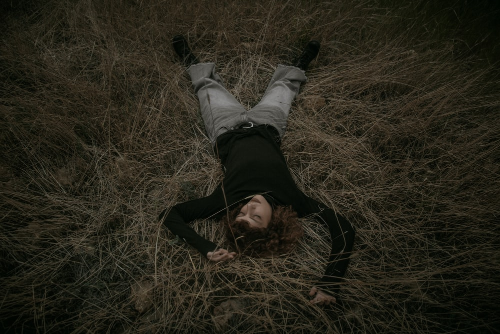 woman lying on dried grass