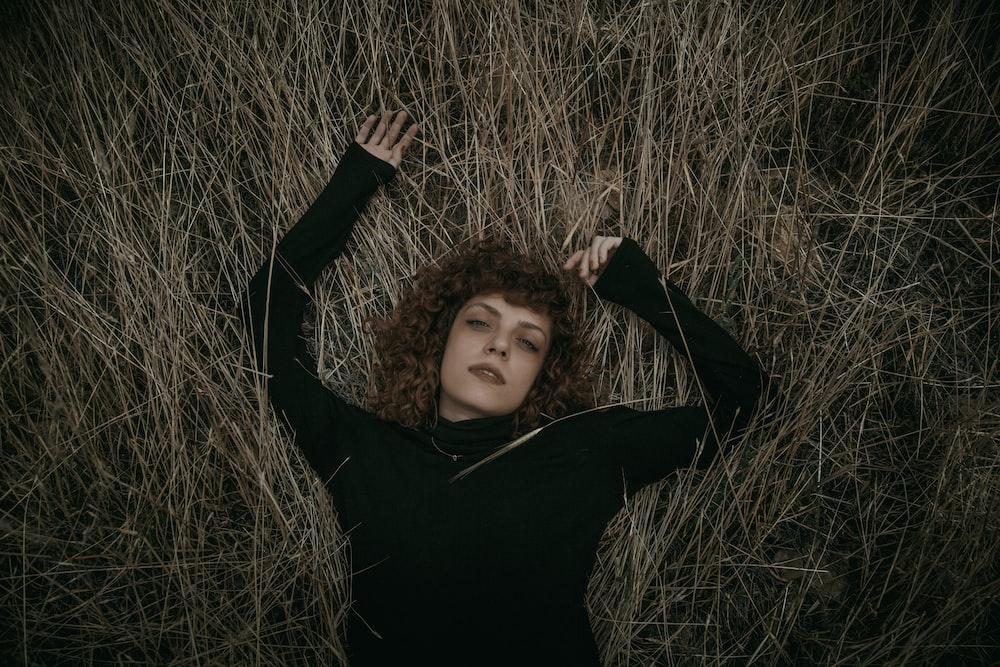 woman in black long-sleeved shirt lying on grassy field
