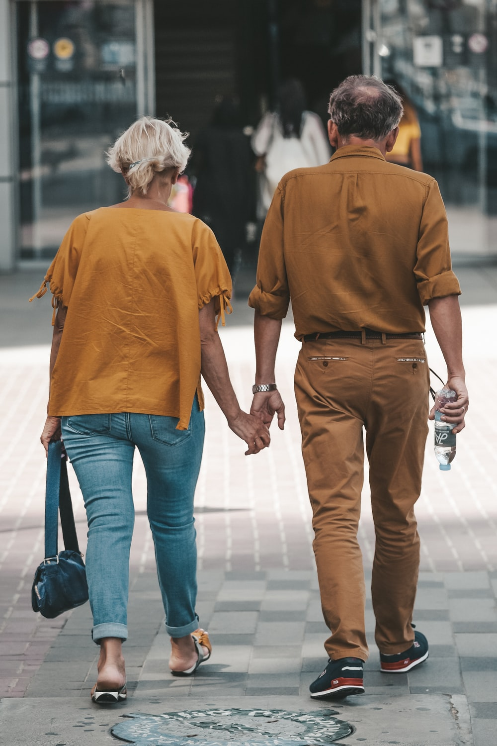 couple holding hands during daytime